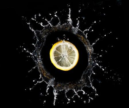 Lemon falling into water on black background Stock fotó