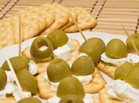 Crackers with olives, cheese feta and basil on white plate  Shallow depth of field  shallow DOF  Stock Photo - 12667075