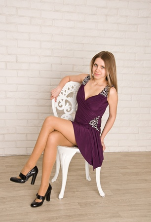 A young female  fashion model in dress sitting on white chair against a brick wall background  She is looking at camera  photo