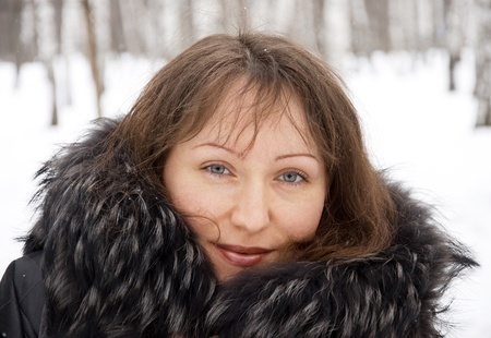 Portrait of beautiful brunette woman in snow winter park