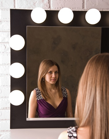 An attractive young woman in dress looking in the mirror Stock Photo