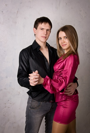 Young love couple dancing against a gray wall.  photo