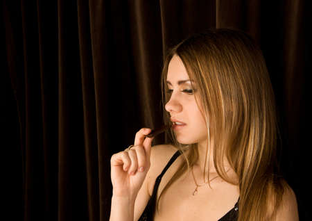 Beautiful young female eating a chocolate bar Stock Photo - 13318279