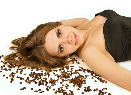 Beautiful woman lie on coffee beans on white background  She is looking at camera  photo
