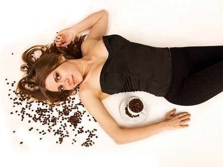 Beautiful woman lie on coffee beans on white background. She is looking at camera.  Stock Photo - 13318281