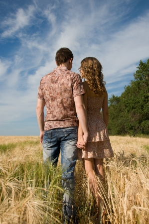 Happy young couple walking on a field - outdoors  photo