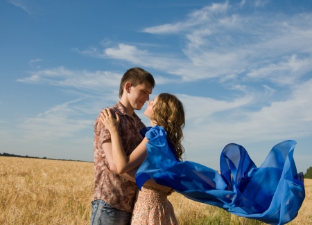 Happy young couple on a field with blue fabric Stock Photo - 14806588