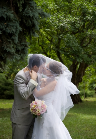 Bride and groom kissing in a park - outdoors photo
