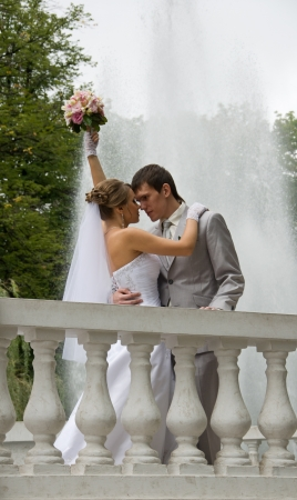 Bride and groom kissing in a street - outdoors photo
