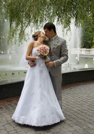 Bride and groom kissing in a street
