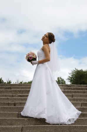 Beautiful bride in white dress against the sky photo
