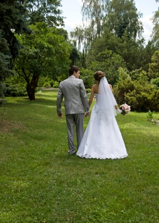 Bride and groom walking in a park - outdoors photo