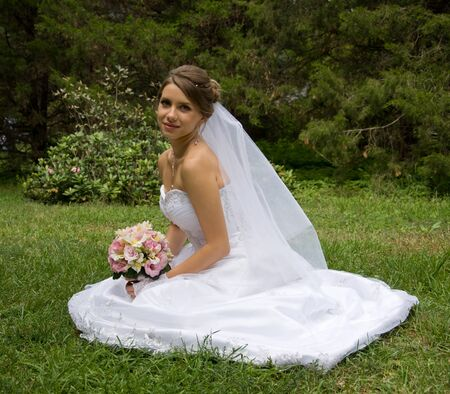 Beautiful bride in white dress sitting on green grass photo