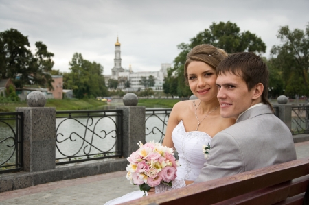 Bride and groom sitting on bench near river