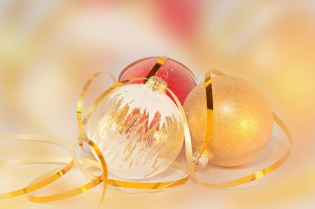 Christmas Bauble and gold ribbon on color background photo