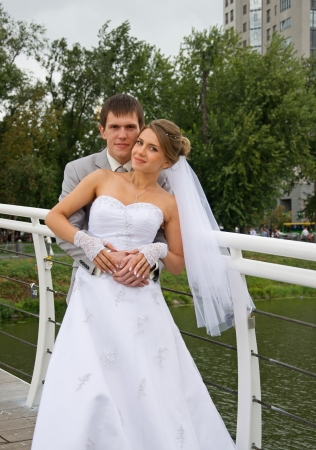 Bride and groom on bridge - outdoors photo