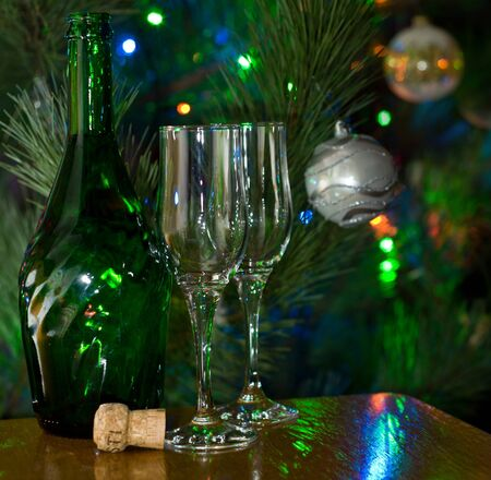 Two glasses and bottle of champagne in front of lighted christmas tree photo