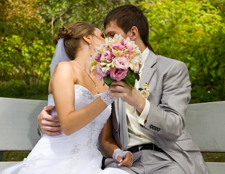 Bride and groom sitting on the bench and kissing photo