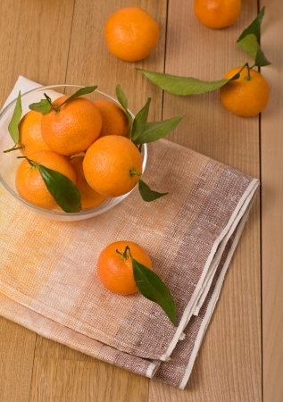 mandarines with leaves in a glass bowl, on wooden table  top view photo