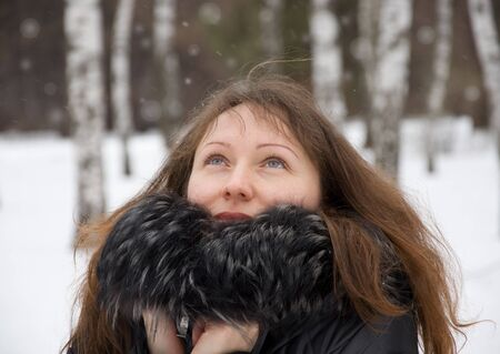 Portrait of beautiful brunette woman in winter park photo