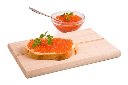 bread with red caviar on a wooden board  Isolated on white photo