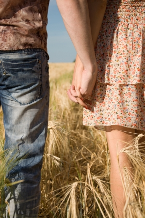 Happy young couple walking on wheat field photo