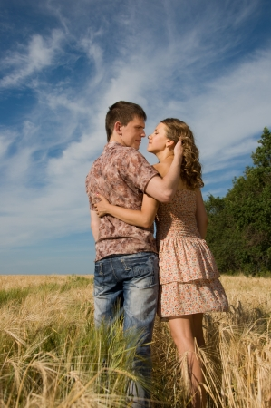 Happy young couple walking on a field - outdoors