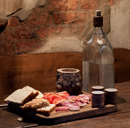 Vodka with bread, bacon and tomato on table photo