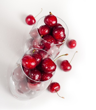 sweet cherries in glasses on white photo