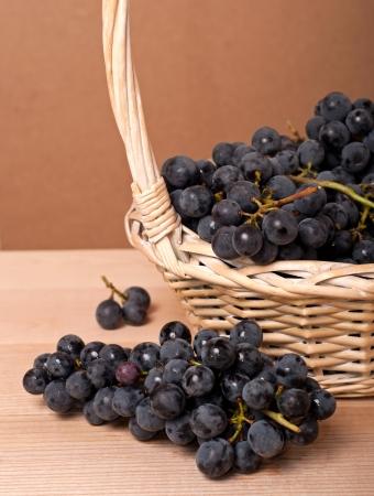cabernet: Las uvas Cabernet en la cesta sobre la mesa de madera Foto de archivo