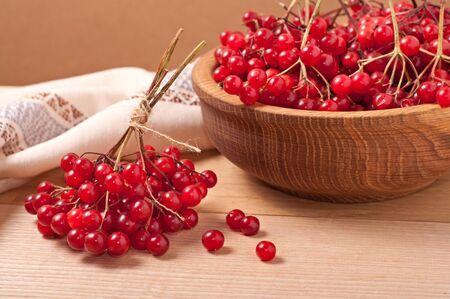 guelder rose berry: Viburnum berries on wooden dish