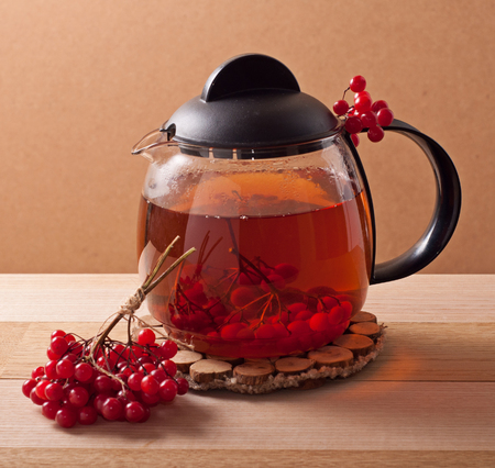 guelder rose berry: Tea with red viburnum berries on wooden table
