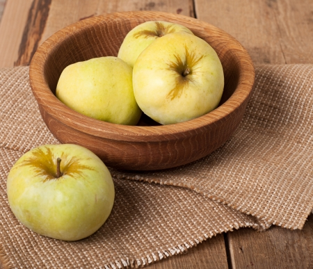 Three apples in dish and one on table