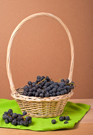 Cabernet Grapes in basket on wooden table photo
