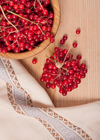 guelder rose berry: Viburnum berries on wooden dish on towel