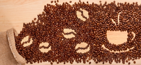 cup of coffee beans on wooden background photo