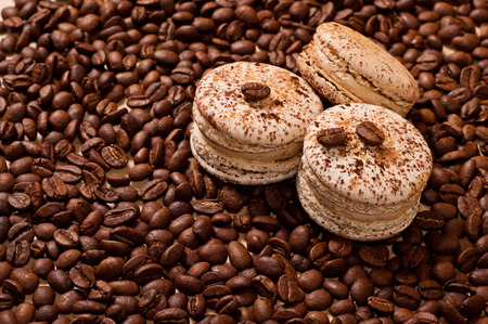 three macaroons on coffee beans background photo