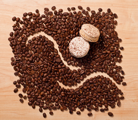 two macaroons on coffee beans background photo
