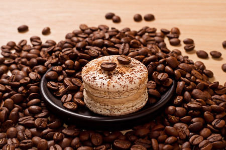 macaroon and coffee beans on black dish on table photo