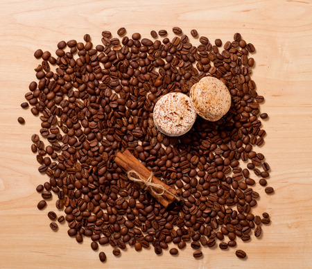 coffee beans, cinnamon and macaroons on wooden background photo