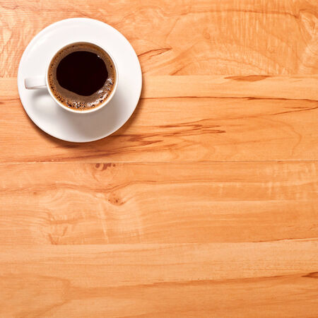 the white coffee cup on wooden background, top view photo