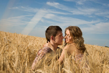 Happy young couple on field on blue sky background photo