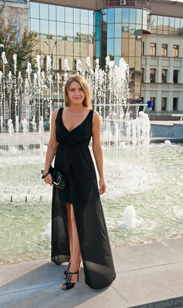 Young beautiful blond woman in black dress near fountain, outdoor photo