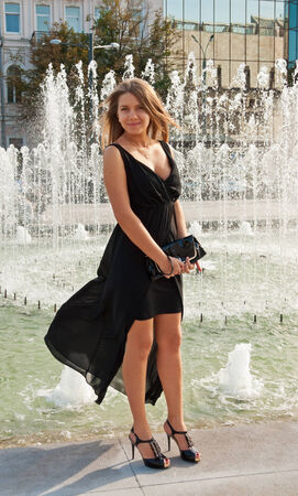 Young beautiful blond woman in black dress near fountain photo