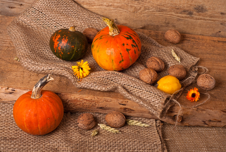Pumpkins, walnut, quince, ear and burlap on wooden background photo