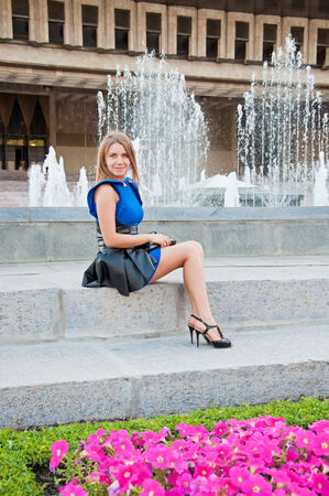 Young beautiful blond woman in blue dress sitting near fountain photo