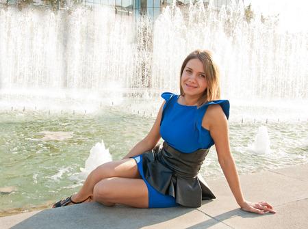 Young beautiful blond woman in blue dress sitting near fountain photo