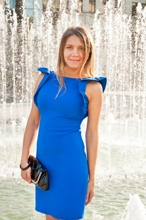 Young beautiful blond woman in blue dress near fountain photo