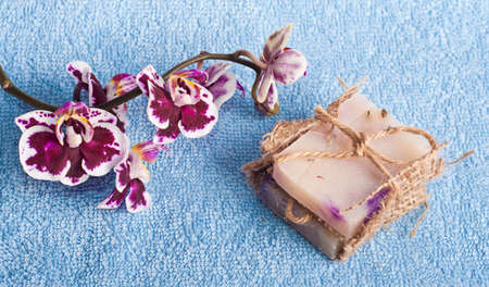 Spa stones, soap and pink orchid on blue background photo