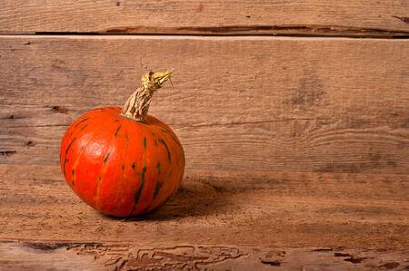The orange pumpkin on old wooden background photo